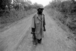 2004, Northern Uganda. Wearing an over-sized uniform and carrying a Kalashnikov, 12-year-old child soldier Omoding Musami patrols a dangerous stretch of the Obalanga Road. © Alixandra Fazzina