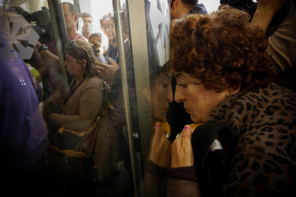 CYPRUS, Nicosia : People queue up outside a Laiki bank branch in the Cypriot capital, Nicosia, on March 28, 2013, as they wait for the bank to open after an unprecedented 12-day lockdown. Queues of dozens of people formed before the doors swung open at 12:00pm (1000 GMT) for the first time since March 16, and there were tensions as a few branches opened late, with customers banging on the doors