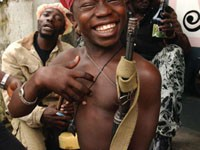 July 2003 - The insouciance of a child soldier drunk, enrolled among combatants of President Charles Taylor during the battle for Monrovia, Libera. Child soldiers were often drugged prior to facing combat by commanders, they where given drugs such as cocaine and amphetamines to make them fight and then hashish, marijuana and alcohol to calm and numb them. © Noël Quidu